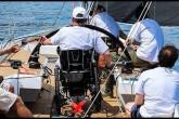 Al timone di una barca da regata, in sedia a rotelle